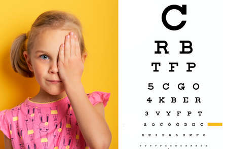eyesight check. girl covering one eye with hand. eyesight check and health examinations.ophthalmology concept. Kid closing one eye with hand against alphabetical out of focus eye test chart in background.