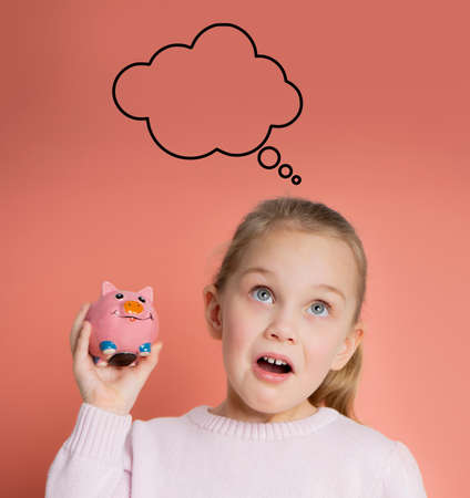 surprised girl with a piggy bank thinking of desires thought cloud on a pink background Standard-Bild