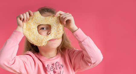 Little cute girl holds a pancake and looks through a hole in it, on a pink background. Sweet breakfast. spring festival carnival. Standard-Bild