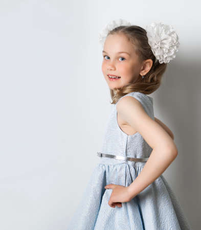 Portrait of an elegant seven-year-old girl in a blue festive dress with hairstyles with bows on a light background. retro style Standard-Bild