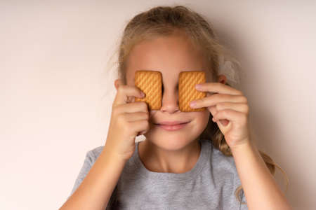 Full of sweet taste. Cute little girl having fun with cookies. The beautiful girl covered her eyes with cookies. Bakery-style cookie recipe. Bakery. Cooking recipe.