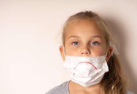 Sad girl in a medical mask. She painted a sad smile on the mask. Standard-Bild