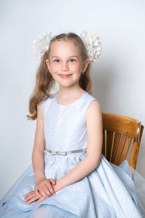 Portrait of an elegant seven-year-old girl in a blue festive dress with hairstyles with bows, sits on a chair on a light background. Retro style Standard-Bild