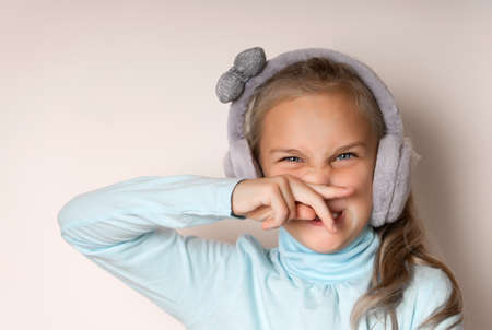 Little girl in fur headphones wipes her nose with her hand
