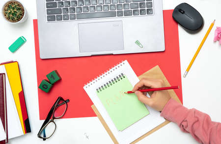 Top view of workspace mockup on red background with notepad, pen, glasses, laptop and accessories. Woman hands write a plan at the beginning of the month