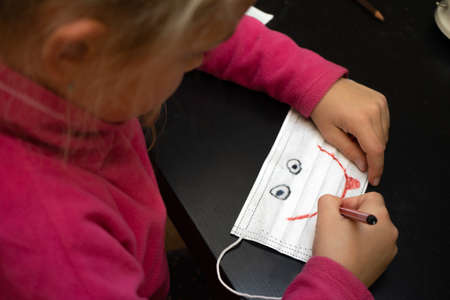 Little girl paints a medical mask. Draws a smile on it and eyes - a smiley. Pandemic Standard-Bild