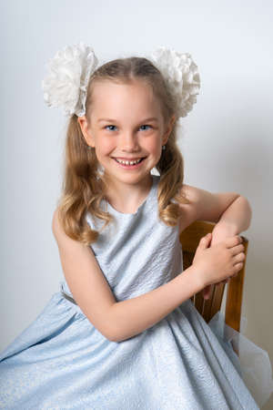 Portrait of an elegant seven-year-old girl in a blue festive dress with hairstyles with bows, leaning on a chair against a light background. Retro style