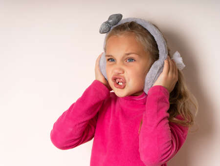 Little cute toothless girl is surprised pretending to listen to music in warm fur headphones on a light background