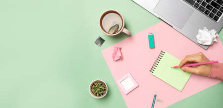 Pastel office table with a laptop, notepad, and a womans hand is writing. Top view with copy space, flat lay.