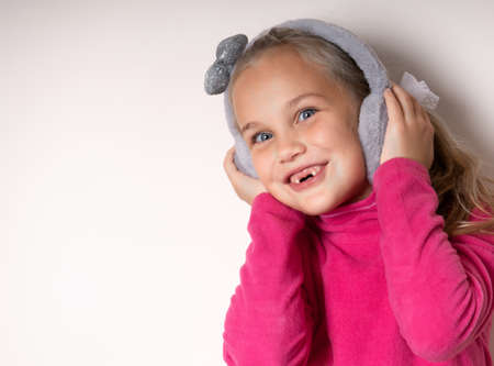 Little cute toothless girl fooling around in warm fur headphones on a light background Standard-Bild