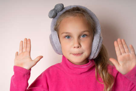 Little cute girl raised two palms up and looks at the camera, she is in warm fur headphones on a light background