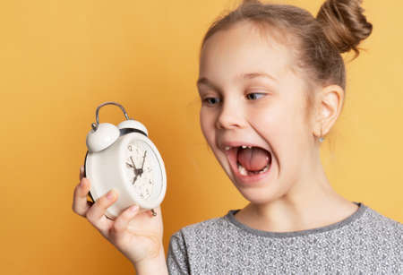 Close up of shocked schoolgirl holding alarm clock and shouting while standing on yellow background. Concept of starting training, ending vacation or starting seasonal discounts.