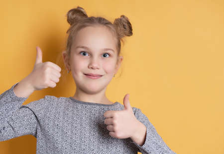 Portrait of cute little girl smiling toothless and showing thumbs up on yellow background. Close-up face of a girl with a cheerful hairstyle. The concept of positive childrens emotions. Banner.