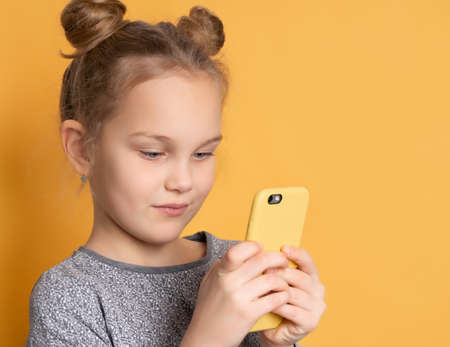 Close up of a concentrated little girl looking at her smartphone while standing on a pink background. Child enjoys playing games on the phone. Place for text.