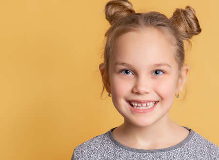 Child shows his healthy teeth. Close up of the face of a little cute girl who is smiling showing teeth on a yellow background. Pediatric dentistry concept. Article. Banner. Place for text.