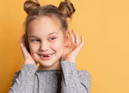 Close up of a little cheerful smiling girl touches her ears and looks away on a yellow background. Concept of fun and sincere childrens emotions. Place for text.