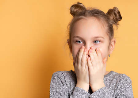 Close up portrait of shocked pretty little girl covering her mouth with hands and looking away. Child poses on a yellow background near the place for text. Concept of school gossip and surprises.