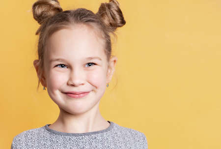 Close up portrait of a Caucasian girl with a satisfied expression who stands on a yellow background and looks away. Blue-eyed child posing in the studio. Place for text.
