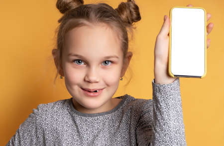 Close up portrait of happy teen girl holding phone and showing blank screen of mobile phone looking at camera. Cheerful girl posing on a yellow background. Concept of modern technology for children.