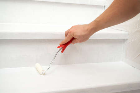 male hand paints a wooden staircase white with paint and a roller. Home renovation Foto de archivo