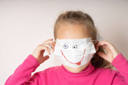 Girl in a medical mask with a painted smile hides her face Foto de archivo