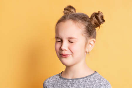 Cute charming funny caucasian blonde girl stands with closed eyes in anticipation of a surprise. Child stands on a bright yellow background. Concept of gifts and happy childhood. Place for text.