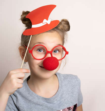 Happy smiling little girl in cute carnival mask with clown nose, paper hat and eyeglasses. Festive costume for masquerade. Female child posing with photo booth accessory studio portrait shot