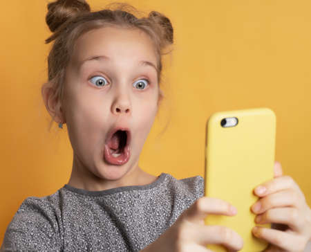 Close up of surprised little girl with wide open mouth looking at phone holding in hands. Portrait of a shocked child on a yellow background. Technology, active lifestyle concept Foto de archivo