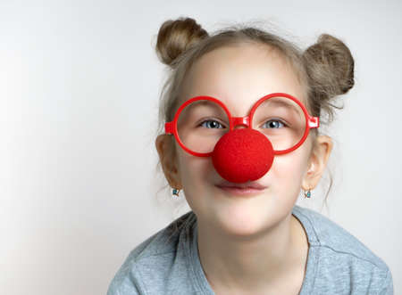 Happy smiling little girl studio headshot portrait isolated on grey background. Cute caucasian female child wearing eyeglasses and clown nose looking at camera. April 1st Foto de archivo