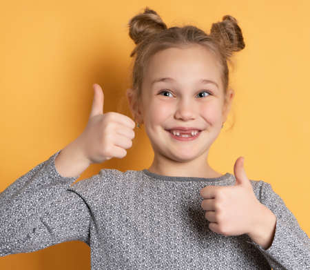Portrait of a cute baby girl smiling toothlessly and showing thumbs up on a yellow background. Close up of a girls face with a cheerful hairstyle. Concept of positive childrens emotions. Banner.