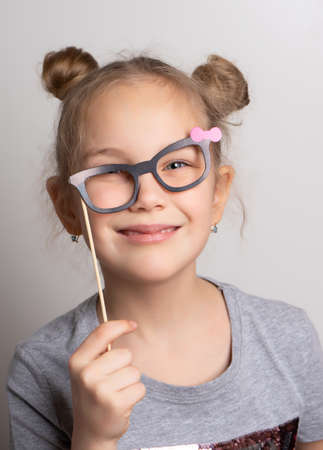 cheerful crazy little girl looks through rickety paper glasses. Festive costume for a masquerade. Attractive female child posing with photo booth accessory studio portrait shot