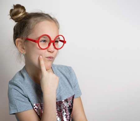 Cute funny little girl with sly squint facial emotion wearing red toy eyeglasses studio headshot portrait isolated on grey background. Beautiful lovely caucasian female child with cute bun hairstyle