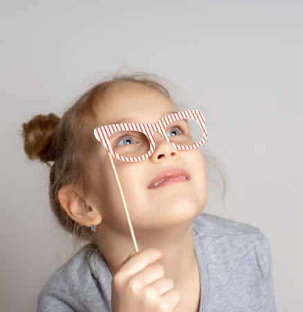 Pensive little girl in carnival mask with paper glasses. Festive costume for a masquerade. Attractive female child posing with photo booth accessory studio portrait shot