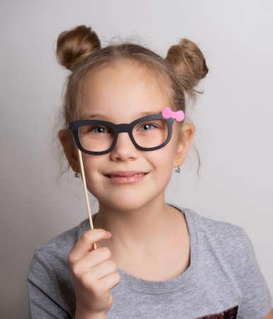 Cute little girl in a carnival mask with paper glasses. Festive costume for a masquerade. Attractive female child posing with photo booth accessory studio portrait shot Foto de archivo
