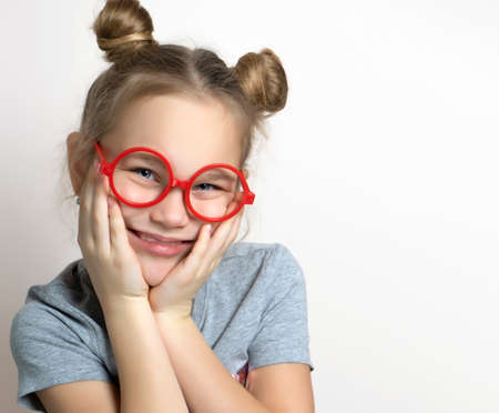 Cute funny little girl with smiling facial emotion wearing red toy eyeglasses touching cheeks studio headshot portrait isolated on grey. Beautiful lovely caucasian female child with cute bun hairstyle