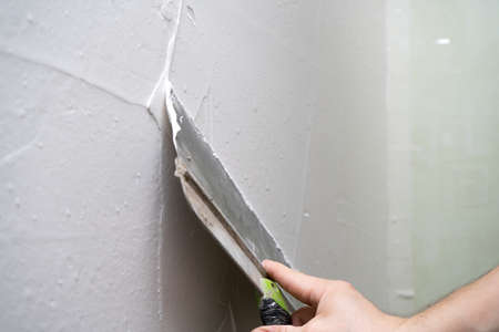 house improvements. putting plaster on the wall with spatula