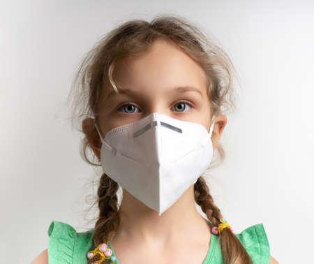 Infection concept. Portrait of little girl wearing medical mask, grey background Foto de archivo