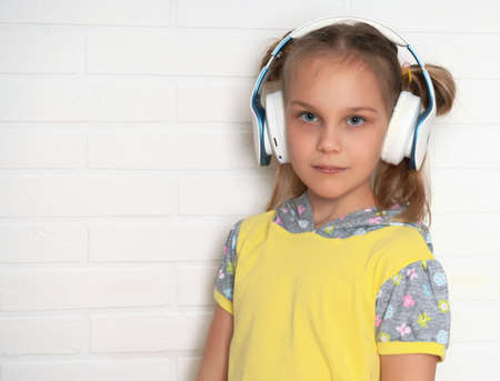 Little girl with headphones and listens to music on the background of a white brick wall