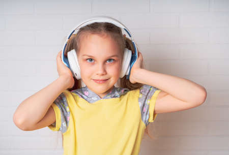 home, technology and music concept - little girl with headphones at home Foto de archivo