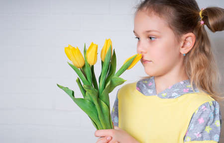 Beautiful young girl in a yellow blouse with tulips flowers in her hands on a light background
