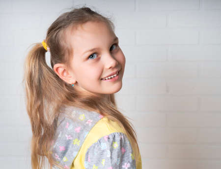 beautiful blond Caucasian young girl in a yellow-gray blouse, looking into the camera with a charming smile, posing in front of a white brick wall. Foto de archivo