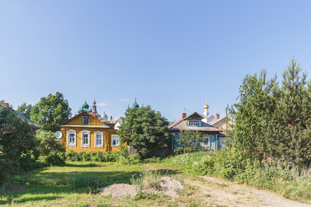 Two wooden houses on the background of the Kremlin in Rostov the Great Фото со стока