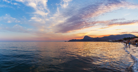sudak: Beach and mountains in the Sudak bay on the Black Sea in the Crimea at sunset Stock Photo