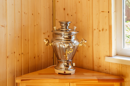 The samovar is electric on a wooden pedestal Stock Photo