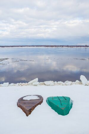 Two boats lie on the snow-covered bank of the river at spring Stock Photo