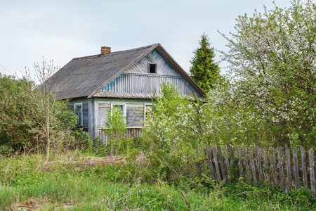 A dirt road with a village house in the summer