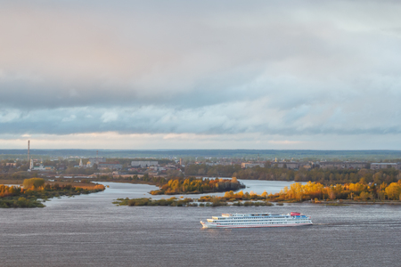 The four-deck ship goes along the Volga at sunset