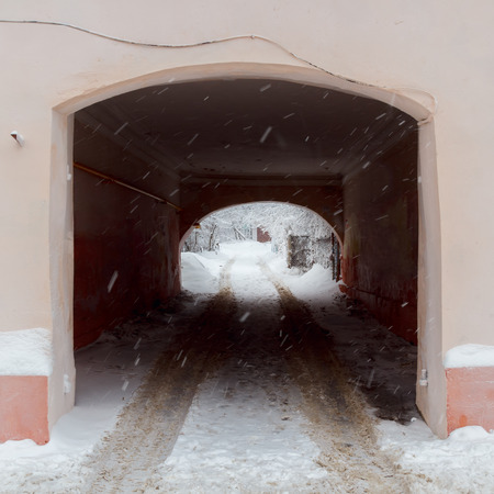 Snowfall on the background of entering the courtyard