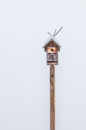 Birdhouse on a white background in winter 스톡 콘텐츠