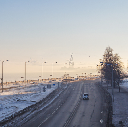Road in the city on the waterfront in winter